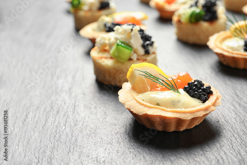 Tasty black caviar appetizers on slate plate Canvas Print
