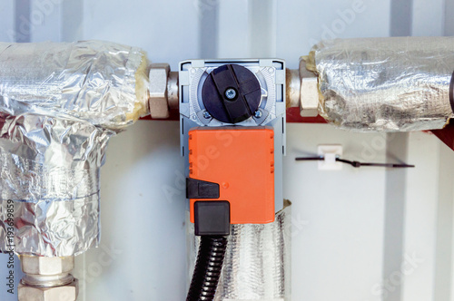 Orange damper actuator installed on the industrial ventilation unit body, front Canvas Print