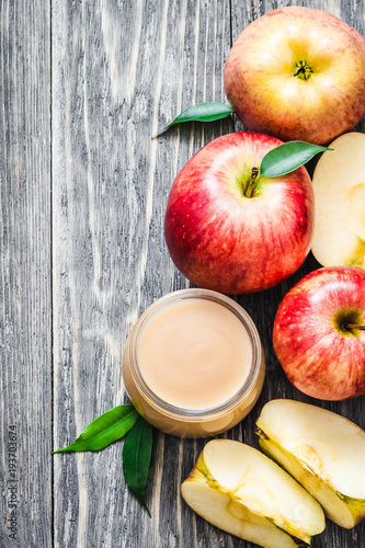 Photo Baby food, applesauce in glass jar and red ripe apples on rustic wooden background