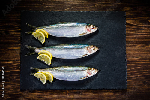 Fresh raw herrings served on black stone on wooden table