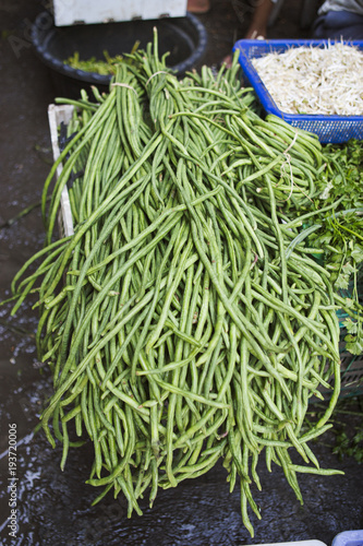 Bundles of long green beans piled up at a farmers market in