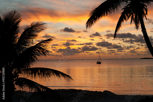Spoed Foto op Canvas Zee zonsondergang Beautiful sunset from the beach in Chub Cay, Bahamas with my sailboat Arcturus in the background.