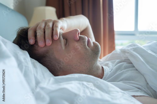 Fototapeta man lying in bed at home suffering from headache or hangover