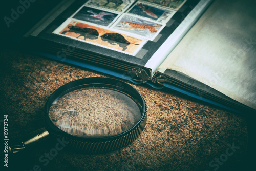 Fotografia  Book with postage stamps and a magnifying glass.