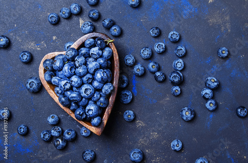 Fotografia Fresh blueberries in a wooden bowl in the shape of a heart on a dark background,