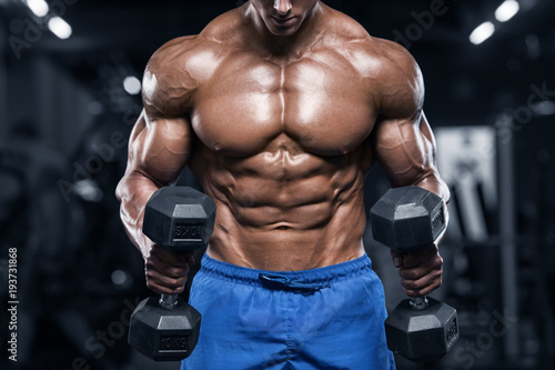 Fotografia  Muscular man working out in gym doing exercises with dumbbells, strong male nake