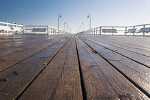 Pier During A Sunny Day - A Closeup Of Wooden  Boards, Seagulls On A Railing
