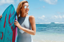 Outdoor Shot Of Active Female Surfer In Shades, Wears Blue Bathing Suit, Holds Surf Board In Front, Going To Have Water Sport Competitions, Stands Back To Ocean With Copy Space For Your Advertising
