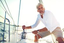 Mature Man Winching Sail Ropes...