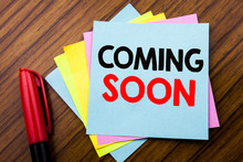 Handwriting Announcement Text Coming Soon.  Concept For Under Construction Written On Sticky Stick Note Paper With Wooden Background With Space Office View With Pencil Marker