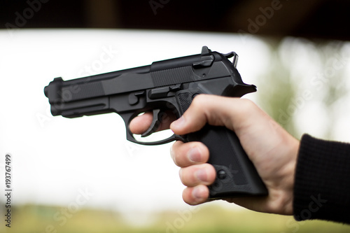 Killer with gun close up over grunge background with copyspace. Wallpaper Mural
