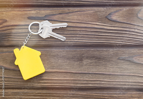 keys, keychain in the form of a house on a wooden background Canvas Print