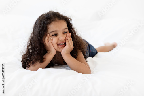 Smiling little girl lying on bed withface on her hands looking away