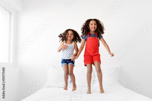 Little girls jumping on bed with big smile