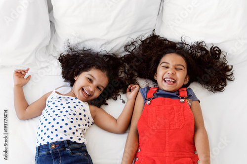 Little girls lying on bed laughing together