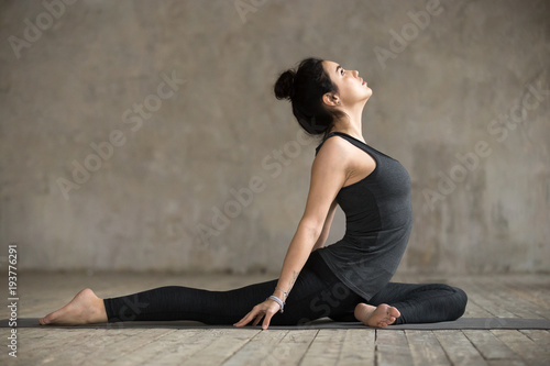 Recess Fitting Yoga school Young woman practicing yoga, doing Single Pigeon, Eka Pada Raja Kapotasana exercise, One Legged King Pigeon pose, working out, wearing sportswear, indoor full length, gray wall in yoga studio