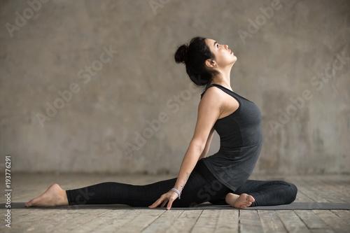 Poster Cygne Young woman practicing yoga, doing Single Pigeon, Eka Pada Raja Kapotasana exercise, One Legged King Pigeon pose, working out, wearing sportswear, indoor full length, gray wall in yoga studio