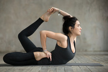 Young Woman Practicing Yoga, Doing Variation Of Dhanurasana Exercise, Bow Pose, Working Out, Wearing Sportswear, Black Pants And Top, Indoor Full Length, Gray Wall In Yoga Studio