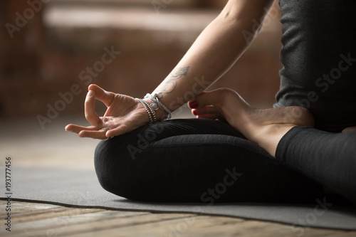 Tuinposter School de yoga Young sporty woman practicing yoga, doing Padmasana exercise, Lotus pose, with mudra gesture, working out, wearing sportswear, black pants and top, indoor close up, yoga studio