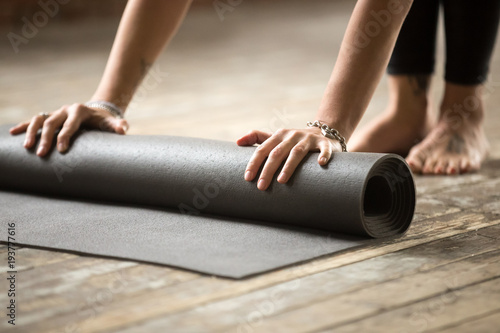 Foto  Hands of attractive young woman unfolding black yoga or fitness mat before working out at home in living room or in yoga studio