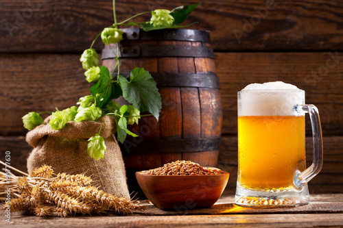 Papiers peints Biere, Cidre Mug of beer with green hops, wheat ears and wooden barrel