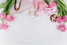 A Composition For Newborns On A Wooden White Background With Clothes, Pink Tulips, Hearts And A Cookies, Copy Space And Flat Lay. It's A Girl.