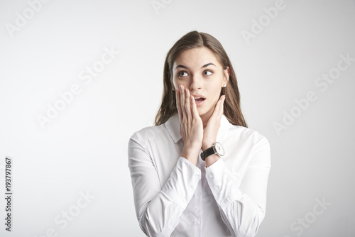 Fotografía  Portrait of happy young businesswoman wearing white shirt while standing with her arms rasied and wondering