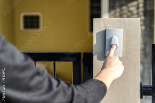 Man's hand pressing a doorbell button with sunlight Tapéta, Fotótapéta