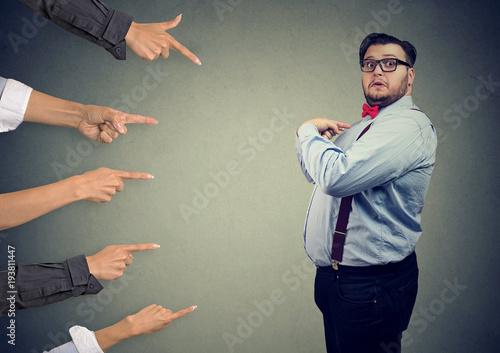 Foto  Besorgter überraschter Geschäftsmann beurteilt von den verschiedenen Leuten, die