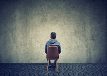 Lonely Man On Chair Against Blank Wall