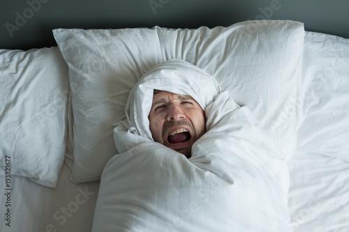 caucasian man rolled in white blanket. Wallpaper Mural