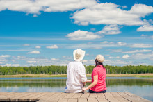 Young Couple With A Fishing Rod Sitting On A Wooden Pier Near The Lake, Rear View