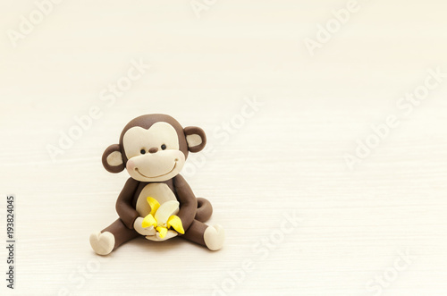 little monkey toy sitting with a banana
