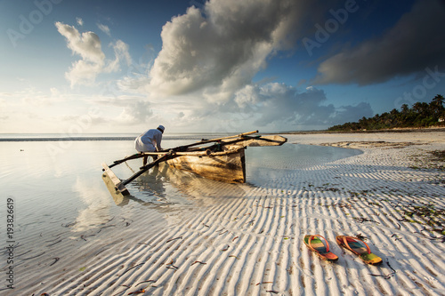 Poster Zanzibar Fishermen going on ocean on traditional fishing boat in Zanzibar with storm clouds at sunrise
