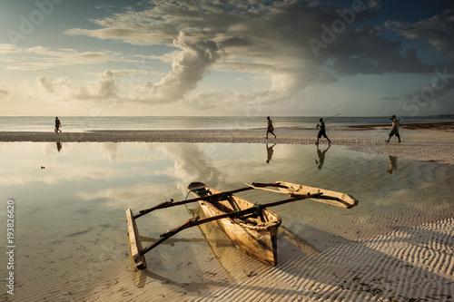 Printed kitchen splashbacks Zanzibar Fishermen going on ocean on traditional fishing boat in Zanzibar with storm clouds at sunrise
