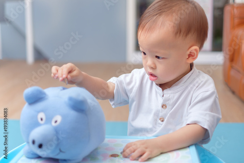 Cute Little Asian 18 Months 1 Year Old Toddler Baby Boy Child Putting Thai Coin Into Blue Piggy Bank Money Savings For Children Financial