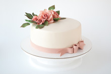 Art Cake Decorated With Pink Flowers And Green Leaves From Mastic On A White Background.