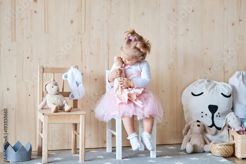 Fotografie, Obraz  Amazing little girl playing with a doll in her room