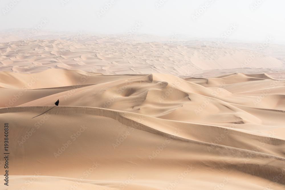 Fototapeta Young beautiful Caucasian woman posing in a traditional Emirati dress - abaya in Empty Quarter desert landscape. Abu Dhabi, UAE.
