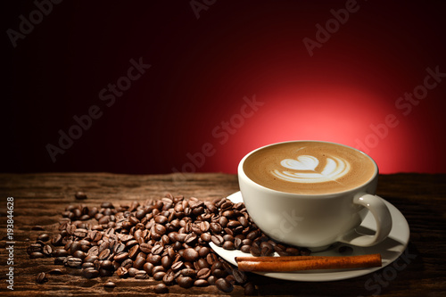 Deurstickers Cafe Cup of coffee latte and coffee beans on reddish brown background