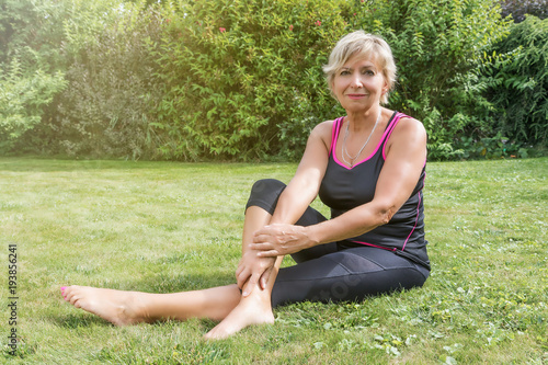Deurstickers Ontspanning Smiling attractive senior blond woman is relaxing after stretching in the garden. Woman is looking at the camera.