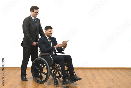 Fotografia, Obraz  The happy businessman and the invalid hold a tablet on the white wall background