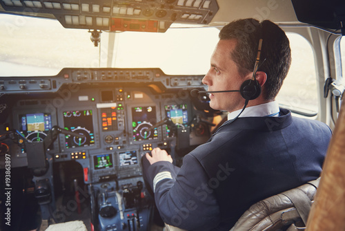 Side view serene pilot talking by headset while situating in cabin with appliances Tapéta, Fotótapéta