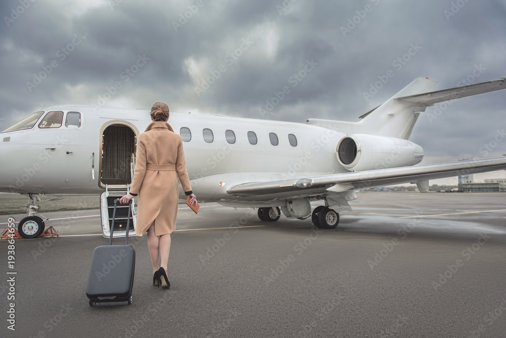 Fototapety, obrazy: Full length female keeping baggage while going to private jet. She turning back to camera. Trip concept
