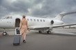 Full length female keeping baggage while going to private jet. She turning back to camera. Trip concept