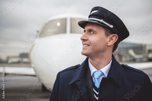 Fotografie, Obraz  Side view beaming young aviator situating opposite aircraft on street