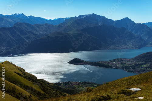 Foto op Canvas Nachtblauw Panoramic View of beautiful landscape in the Italian Alps with fresh green meadows and snow-capped mountain tops in the background on a sunny day with blue sky and clouds in springtime.