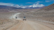 Altiplano region Bolivia with snow covered volcano and offroad car driving through the landscape