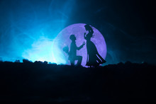 Amazing Love Scene. Silhouettes Of Man Making Proposal To Woman Or Silhouettes Of Couple Against Big Moon At Background
