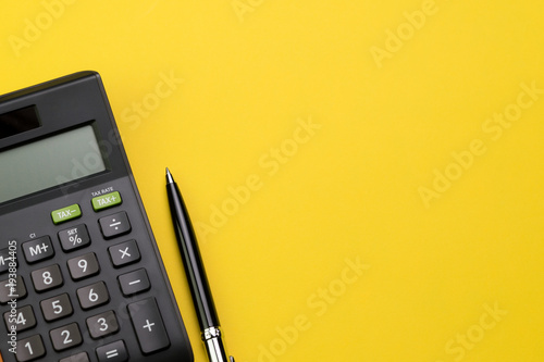 Fotografía  Flat lay or top view of black pen with calculator on vivid yellow background tab